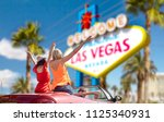 summer holidays, road trip and travel concept - happy friends driving in convertible car and waving hands over welcome to fabulous las vegas sign background - stock photo