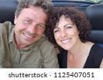 smiling couple in convertible...   Shutterstock . vector #1125407051