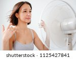 woman refreshing in front of a... | Shutterstock . vector #1125427841