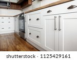 Stock photo stylish light gray handles on cabinets close up kitchen interior with modern furniture and 1125429161