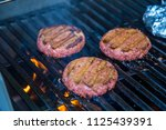 hamburger on grill grilling... | Shutterstock . vector #1125439391