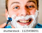 a man shaves his beard with a... | Shutterstock . vector #1125458051