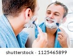 a handsome man shaves his beard ... | Shutterstock . vector #1125465899
