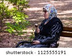 Small photo of Niska Banja, Serbia - July 02, 2018: Muslim old woman on bench relaxing and eats ice cram in shade in nature park. Vacation and enjoyment of the summer concept