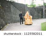bridegroom helps walking bride... | Shutterstock . vector #1125582011