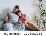 sad couple in bed looking at... | Shutterstock . vector #1125663161