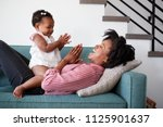 mother lying on sofa at home... | Shutterstock . vector #1125901637