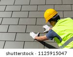 roof repair  worker with white... | Shutterstock . vector #1125915047