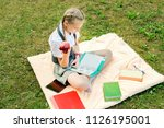 student in uniform eating a red ... | Shutterstock . vector #1126195001