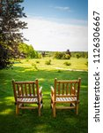 two wooden chairs on lush green ... | Shutterstock . vector #1126306667