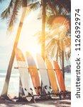 many surfboards beside coconut... | Shutterstock . vector #1126392974