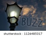 Small photo of Conceptual hand writing showing Buzz. Business photo showcasing Hum Murmur Drone Fizz Ring Sibilation Whir Alarm Beep Chime Light post blue sky enlighten ideas message feelings thought.