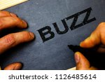 Small photo of Word writing text Buzz. Business concept for Hum Murmur Drone Fizz Ring Sibilation Whir Alarm Beep Chime Man hold holding black marker markers notebook wood wooden background.