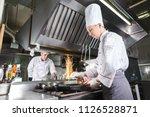 chef in restaurant kitchen at... | Shutterstock . vector #1126528871