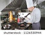 chef in restaurant kitchen at... | Shutterstock . vector #1126530944