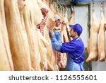 butcher cutting pork  at the... | Shutterstock . vector #1126555601