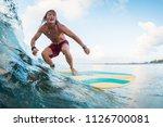 young surfer rides ocean... | Shutterstock . vector #1126700081