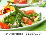 Extreme closeup of plate of asparagus, snow pea and tomato salad with ginger dressing. Glass of white wine out of focus. shallow dof. - stock photo