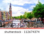 bicycles lining a bridge over... | Shutterstock . vector #112674374