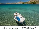small boat in turquoise water... | Shutterstock . vector #1126938677