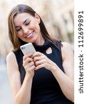 Happy businesswoman texting on her cell phone - stock photo