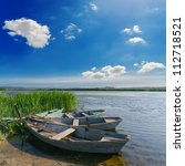 beautiful river and old boats near green grass under cloudy sky - stock photo