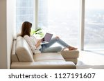 Stock photo relaxed woman using laptop in luxury home living room with big window enjoying working internet 1127191607