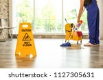 Small photo of Safety sign with phrase Caution wet floor and cleaner indoors. Cleaning service