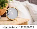 analog alarm clock on table in... | Shutterstock . vector #1127320571