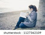 portrait of young woman reading ... | Shutterstock . vector #1127362109