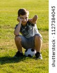 Unhappy boy sitting on a football. Lost a game concept - stock photo