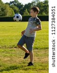 Pre-teen boy playing with a football in a park - stock photo