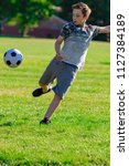 Pre-teen boy playing football in a park - stock photo