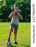Pre-teen boy with a football in a park - stock photo
