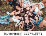 six girls lie on the grass and... | Shutterstock . vector #1127415941