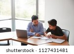 Small photo of High School Tutor Giving Male Student With Laptop One To One Tuition At Desk