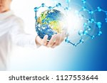 molecules and globus in hand ... | Shutterstock . vector #1127553644