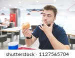 student with a beard sits with... | Shutterstock . vector #1127565704