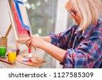elderly woman is painting in... | Shutterstock . vector #1127585309
