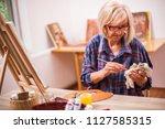 elderly woman is painting in... | Shutterstock . vector #1127585315