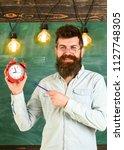 bearded hipster holds clock ... | Shutterstock . vector #1127748305