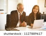 Small photo of Professional senior businessman teaching or training a lady trainee for data summarize report