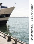 ship anchored to dock with a... | Shutterstock . vector #1127909084