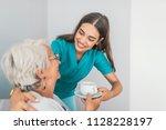 pretty helpful carer talking... | Shutterstock . vector #1128228197