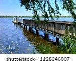 wooden dock extending out into... | Shutterstock . vector #1128346007