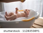 mother bathing her son in white ... | Shutterstock . vector #1128353891