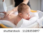 mother bathing her son in white ... | Shutterstock . vector #1128353897