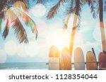 many surfboards beside coconut... | Shutterstock . vector #1128354044
