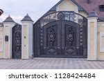 forged black swing gates in the ... | Shutterstock . vector #1128424484