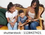 black mother reading to her... | Shutterstock . vector #1128427421